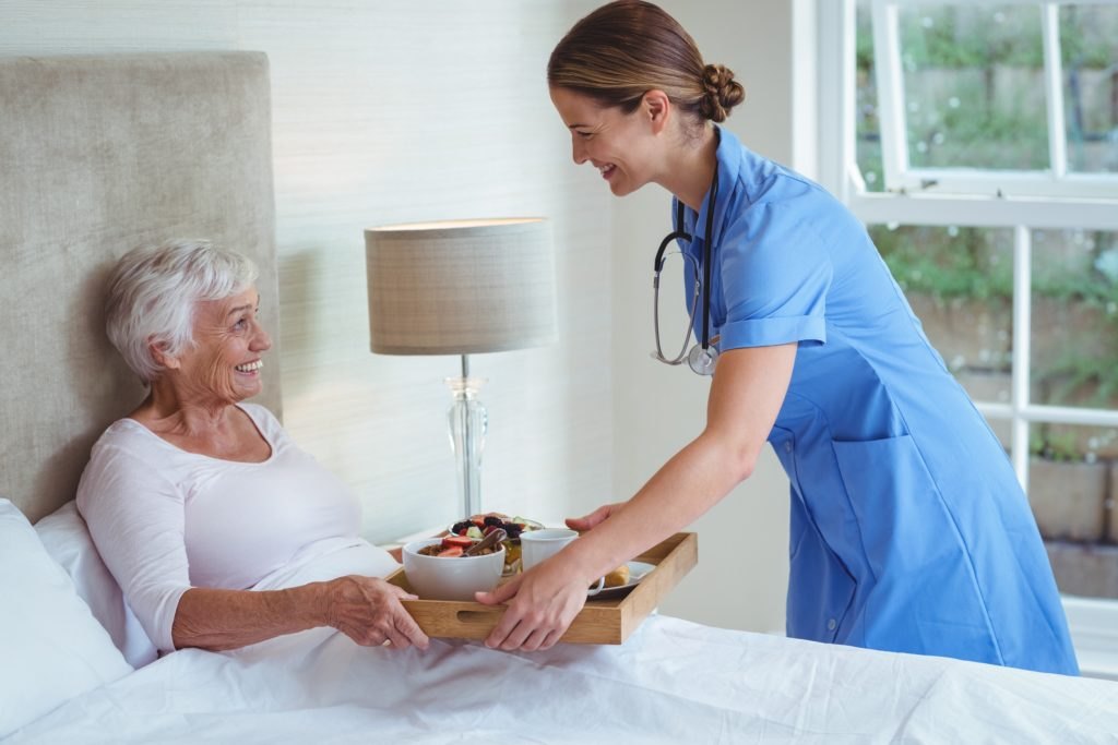 Smiling nurse giving food to senior woman
